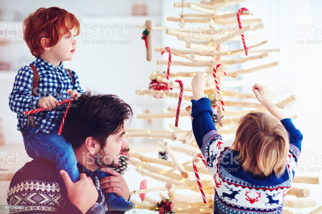 happy family decorates an extraordinary christmas tree made of branches and driftwood at home