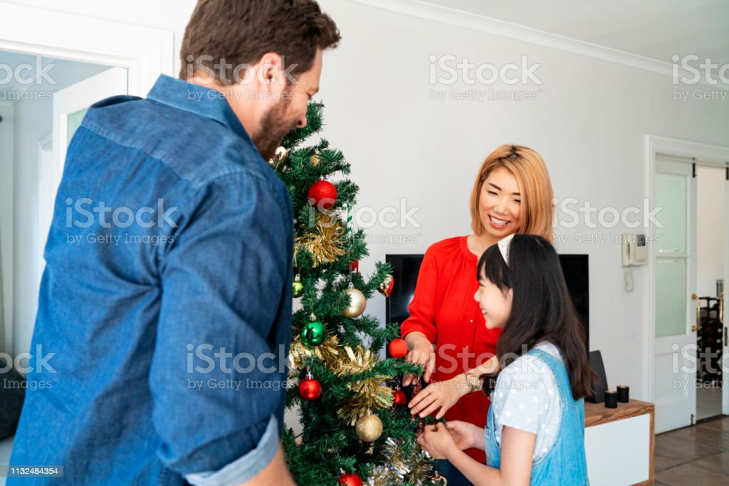 Happy parents decorating Christmas tree with daughter. Family is...