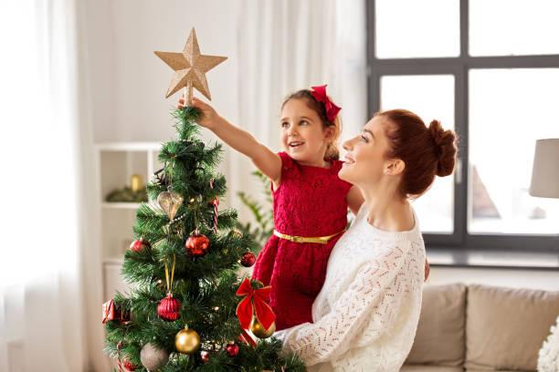 happy family decorating christmas tree at home stock photo