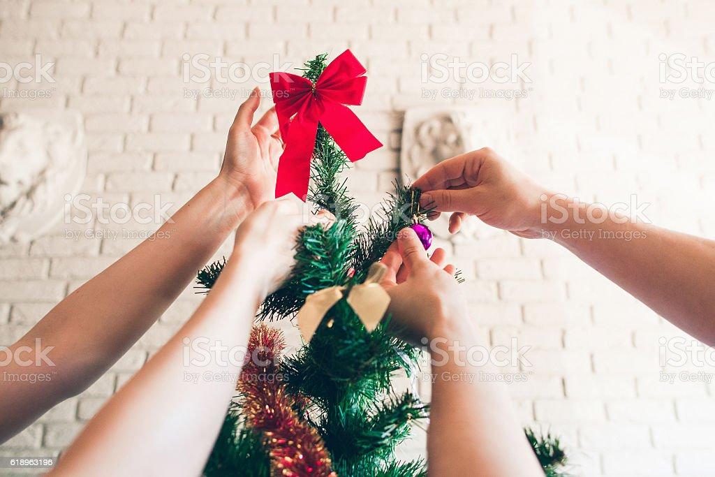 Happy family decorating Christmas tree, close-up stock photo