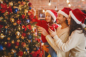 Happy family of three in red Santa hats decorating xmas tree with bubbles and lights at home