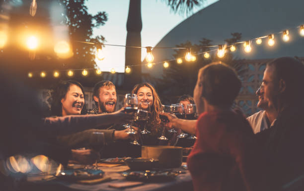 happy family dining and tasting red wine glasses in barbecue dinner party - people with different ages and ethnicity having fun together - youth and elderly parents and food weekend activities concept - vacations food stock pictures, royalty-free photos & images