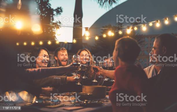 Photo of Happy family dining and tasting red wine glasses in barbecue dinner party - People with different ages and ethnicity having fun together - Youth and elderly parents and food weekend activities concept