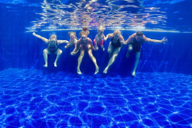 Happy family dive in swimming pool stock photo