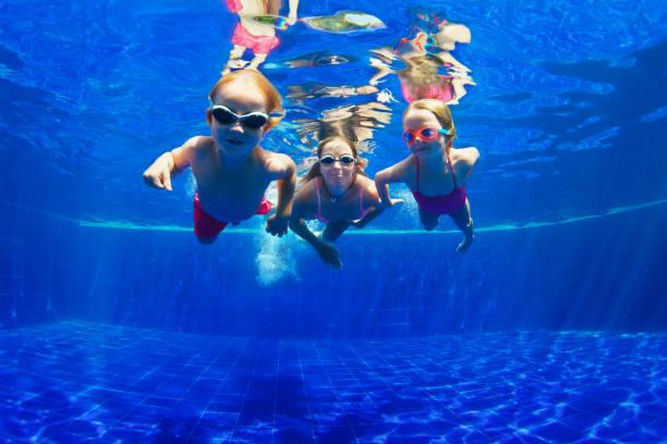 feliz familia inmersión bajo el agua en piscina - natación fotografías e imágenes de stock