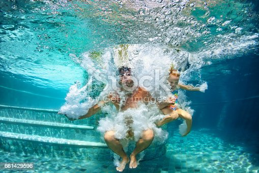 istock Happy family diving underwater with fun in swimming pool 661429596
