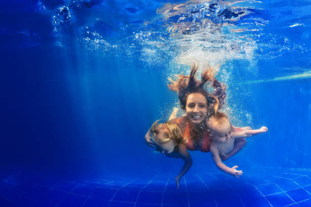 Happy family diving underwater with fun in swimming pool stock photo