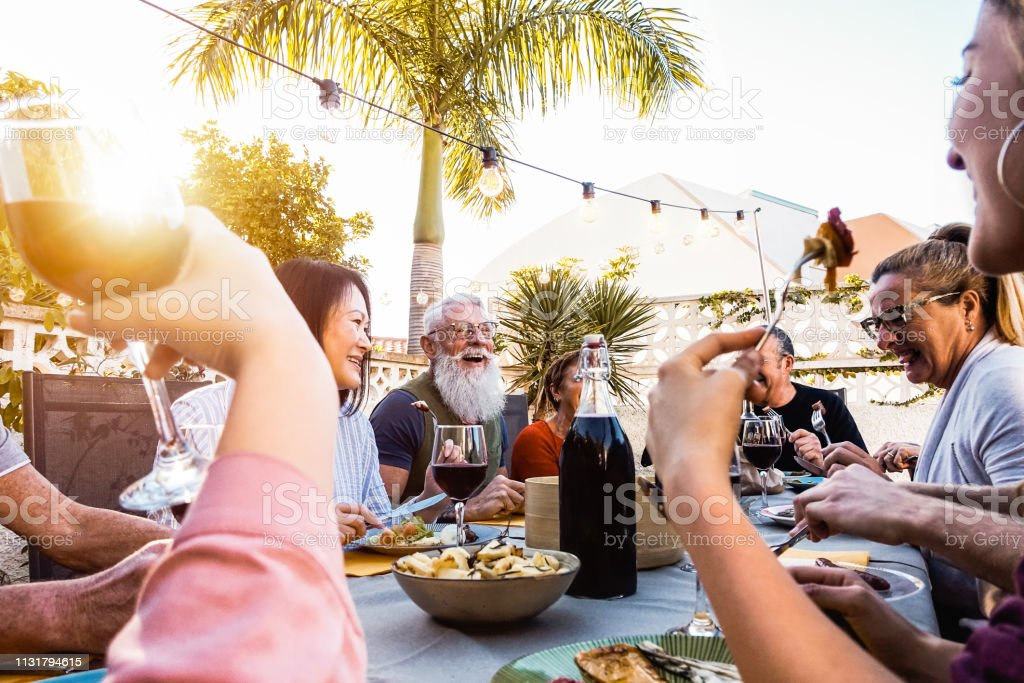 Happy family doing a dinner during sunset time outdoor - Group of diverse friends having fun dining together outside - Concept of lifestyle people, food and weekend activities royalty-free stock photo