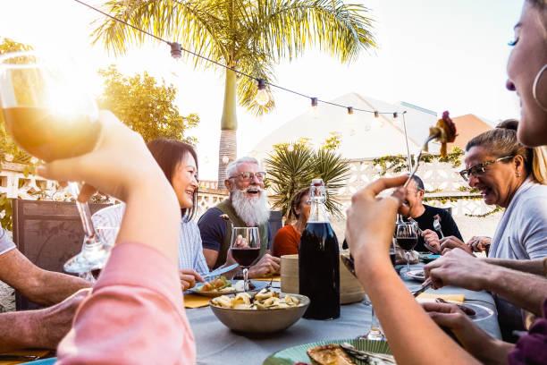 glückliche familie bei einem abendessen im freien-gruppe von verschiedenen freunden, die spaß am gemeinsamen essen im freien haben-konzept der lifestyle-menschen, essen und wochenendaktivitäten - palmengarten stock-fotos und bilder