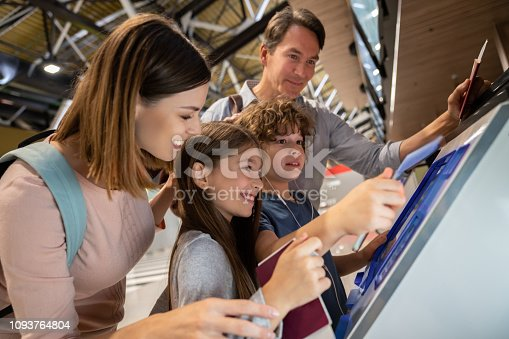 Happy family doing the  self check-in at the airport using a machine and printing their boarding pass - travel concepts
