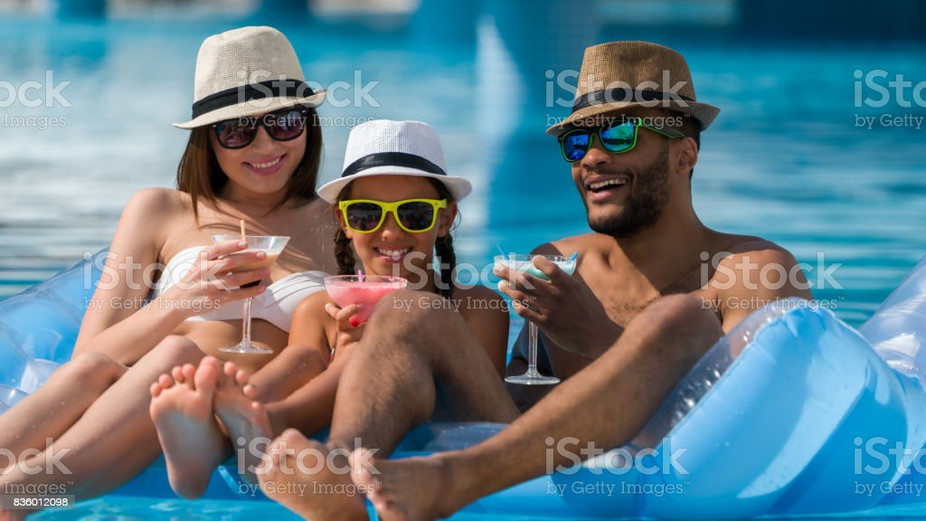 Happy family drinking coktail  in swimming pool stock photo