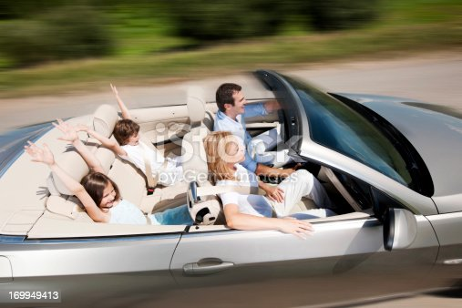829619540 istock photo Happy family driving in a convertible car 169949413