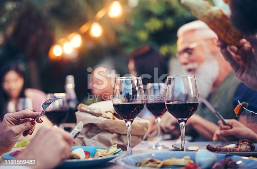 Happy family eating and drinking red wine at dinner barbecue party outdoor - Mature and young people dining together on rooftop - Youth and elderly weekend lifestyle activities - Focus on wineglass