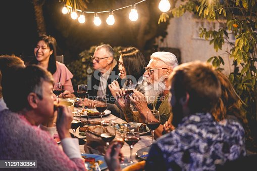 Happy family eating and drinking wine at barbecue dinner outdoor - Multiracial mature and young people having fun at bbq sunday meal - Food and summer lifestyle concept - Focus on tattoo man hands