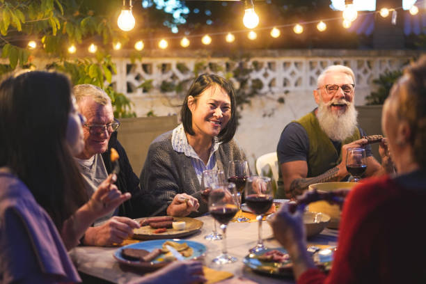 Happy family eating and drinking wine at barbecue dinner outdoor - Multiracial mature and young people having fun at bbq sunday meal - Food and summer lifestyle concept - Focus on asian woman face stock photo