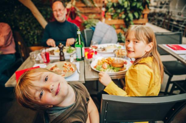 Glückliche Familie Hamburger mit Pommes Frites und Pizza im Restaurant unter freiem Himmel essen – Foto