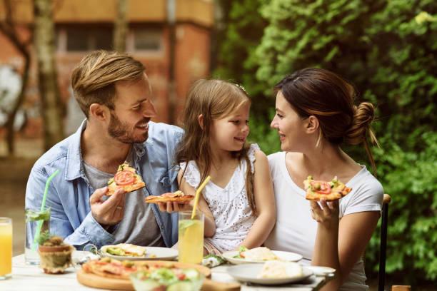 familia feliz comiendo en un restaurante - couple lunch outdoors fotografías e imágenes de stock