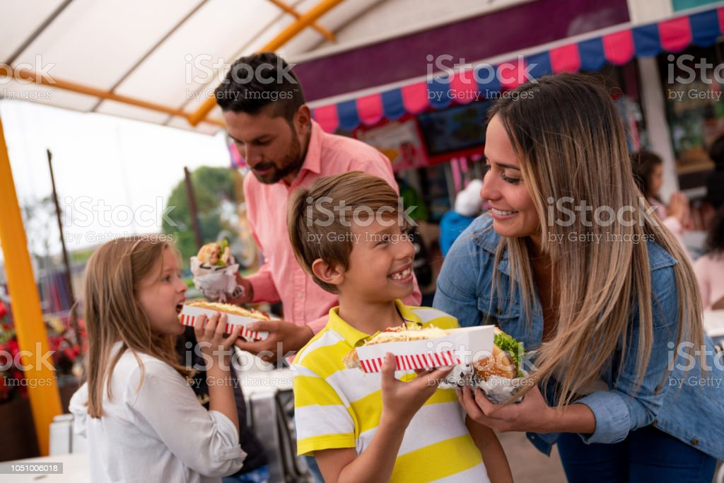 Happy family eating junk food at an amusement park - Stock image .