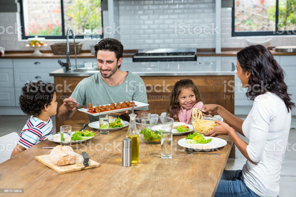 Happy family eating together in the kitchen foto stock royalty-free