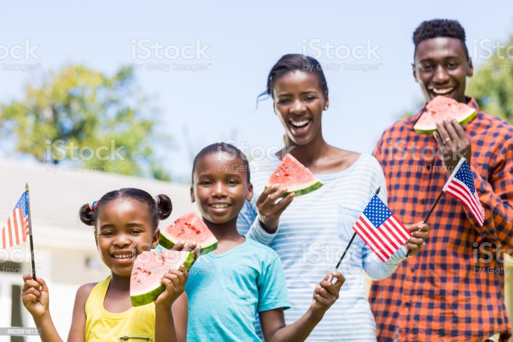 Happy family eating watermelon and showing usa flag stock photo