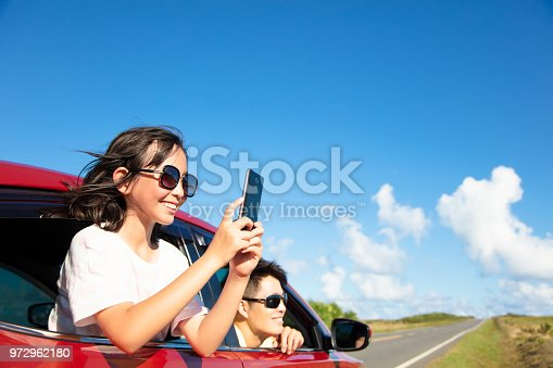 972962180 istock photo Happy family enjoy road trip taking picture by smart phone 972962180