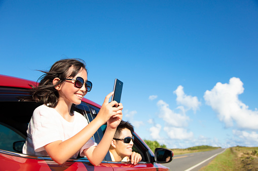istock Happy family enjoy road trip taking picture by smart phone 972962180