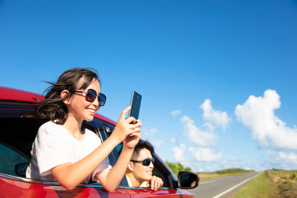 happy family enjoy road trip taking picture by smart phone - asian travel in car stock photos and pictures