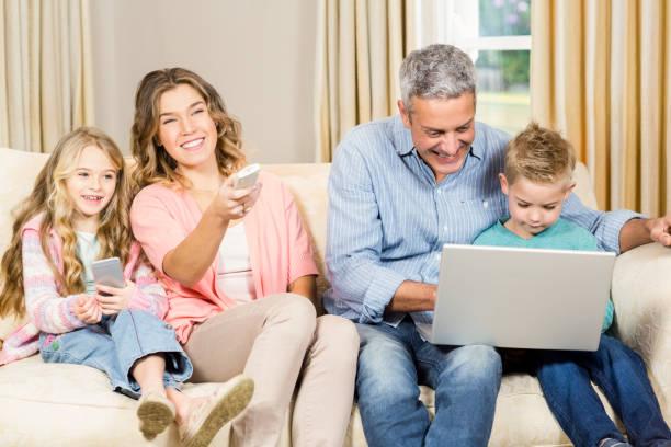 happy family enjoying a movie together - tv e familia e ecrã imagens e fotografias de stock
