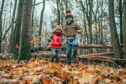 515278306 istock photo Happy family enjoying autumn in forest 1161200862