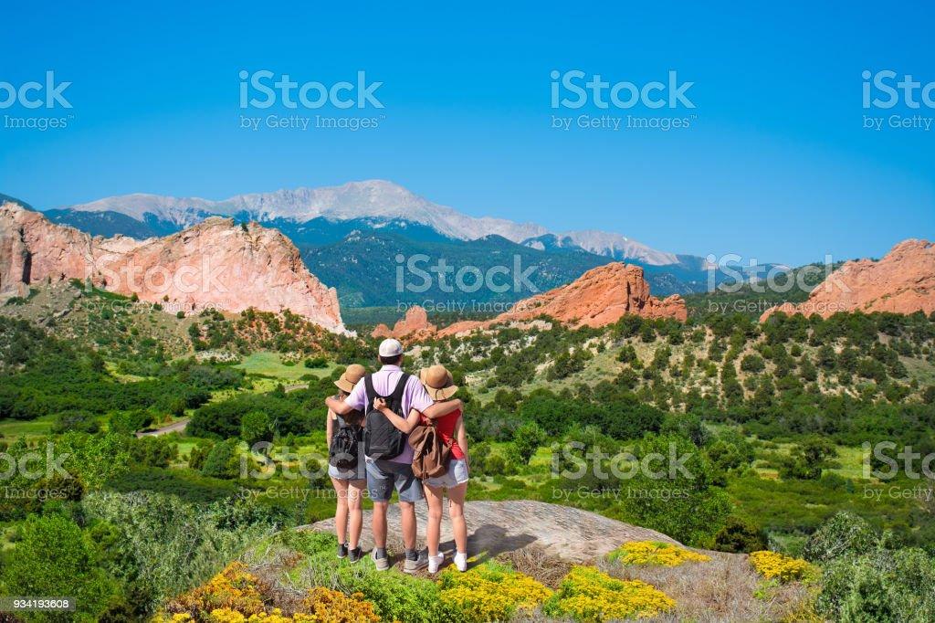 Happy family enjoying beautiful mountain view on vacation hiking trip. stock photo