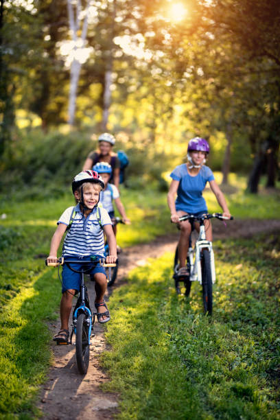 Happy family enjoying bicycle ride in park stock photo