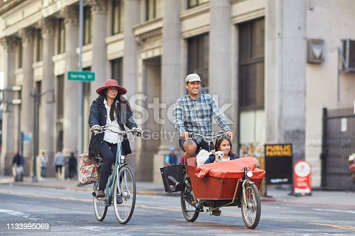 Happy family enjoying bicycle ride on street. Girl and dog are sitting in cart. They are traveling in city.
