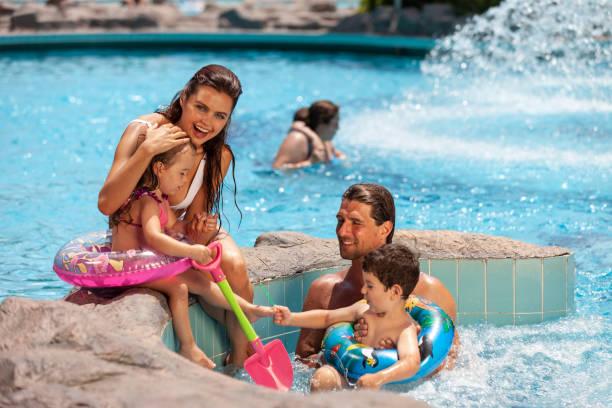 Happy family enjoying near pool stock photo