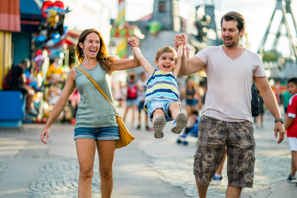 happy family enjoying summer day in amusement park - carnival stock photos and pictures
