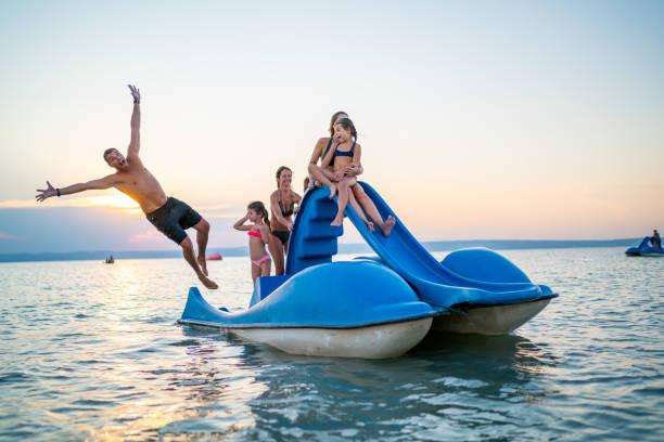 Feliz familia disfrutando verano puesta de sol en el lago con barco a pedales - foto de stock