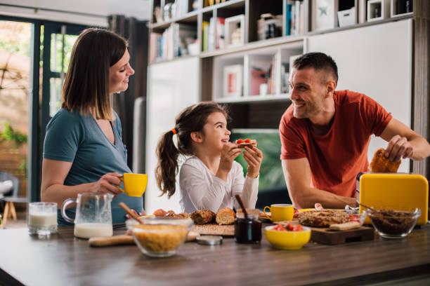 feliz familia disfrutando de su desayuno el fin de semana por la mañana - desayuno fotografías e imágenes de stock