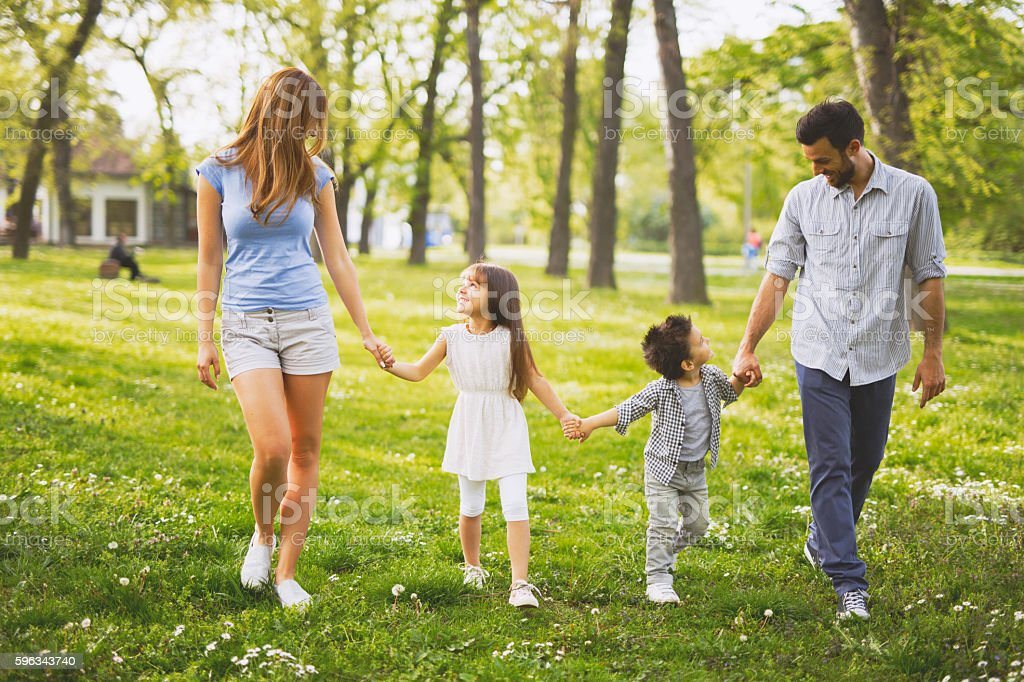 Happy family enjoying their summer day walk in park. royalty-free stock photo