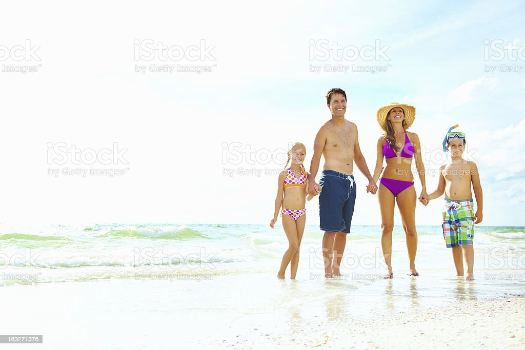 Happy family enjoying time on the beach royalty-free stock photo
