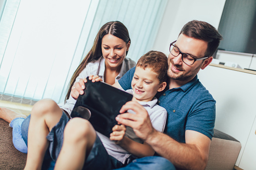 871175856 istock photo Happy family enjoying together at home, using tablet and having great time together. 1209648234