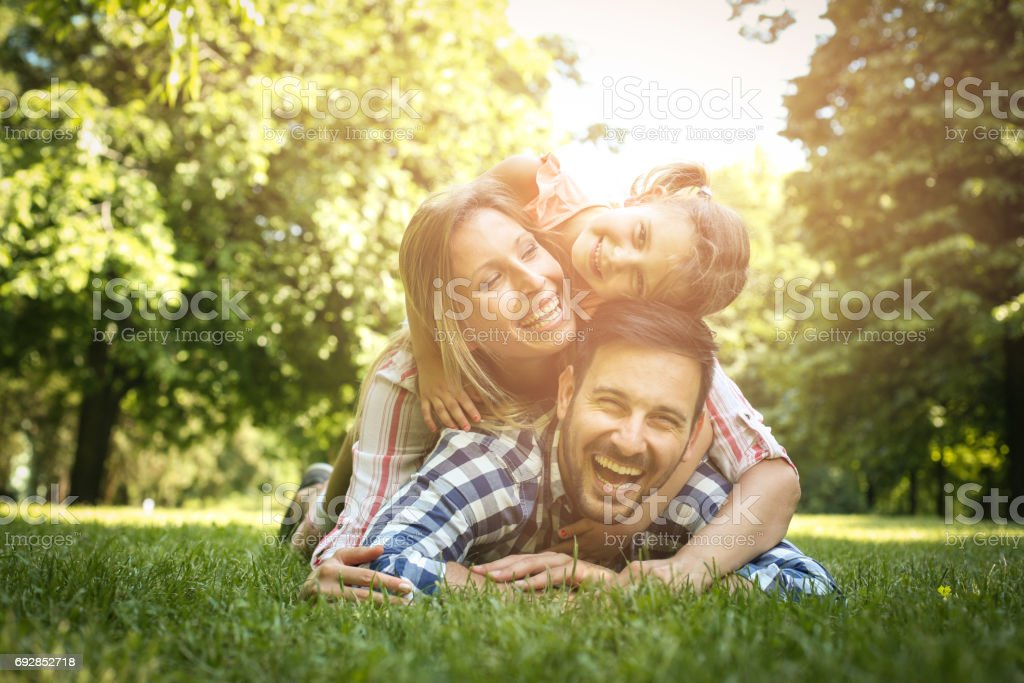 Happy family enjoying together in summer day. Family lying on grass. Mother and daughter lying on father piggyback. stock photo