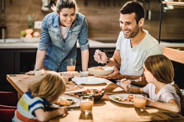 Mutlu aile yemek odasında öğle yemeği yerken zevk. stok fotoğrafı