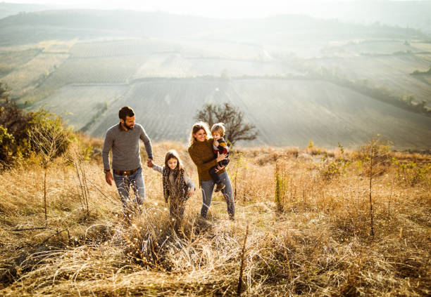 Happy family enjoying while walking up the hill in autumn day. stock photo