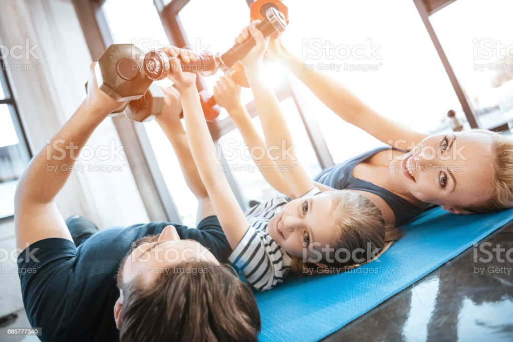 Happy family exercising with dumbbells at fitness studio,  dumbbells in heart shape royalty-free stock photo