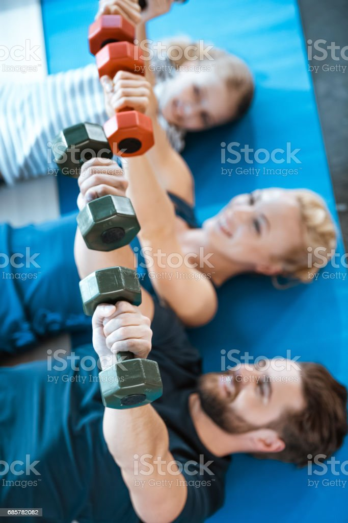 Happy family exercising with dumbbells at fitness studio 免版稅 stock photo