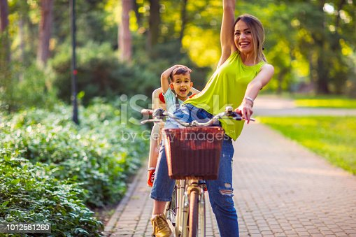 istock Happy family Family sport and healthy lifestyle- Boy on bike with mother - lovely family having quality time outdoors 1012581260