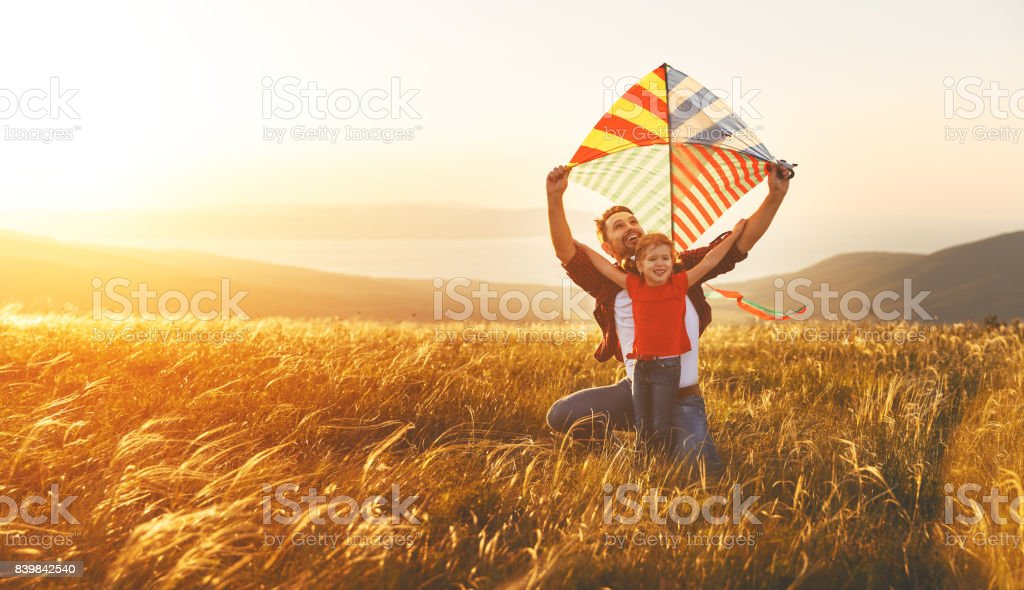 happy family father and baby daughter launch  kite on meadow - foto stock