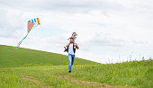 happy family father and baby daughter run with a kite on meadow