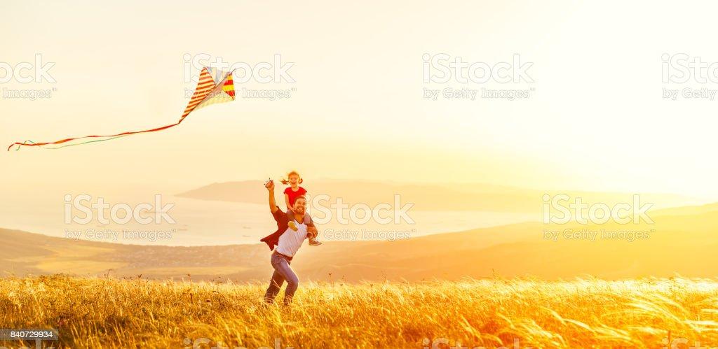 père de famille heureux et la petite fille courir avec cerf-volant sur Prairie - Photo