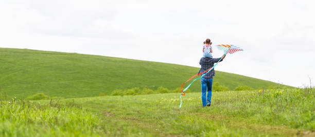 happy family father and baby daughter run with  kite on meadow stock photo