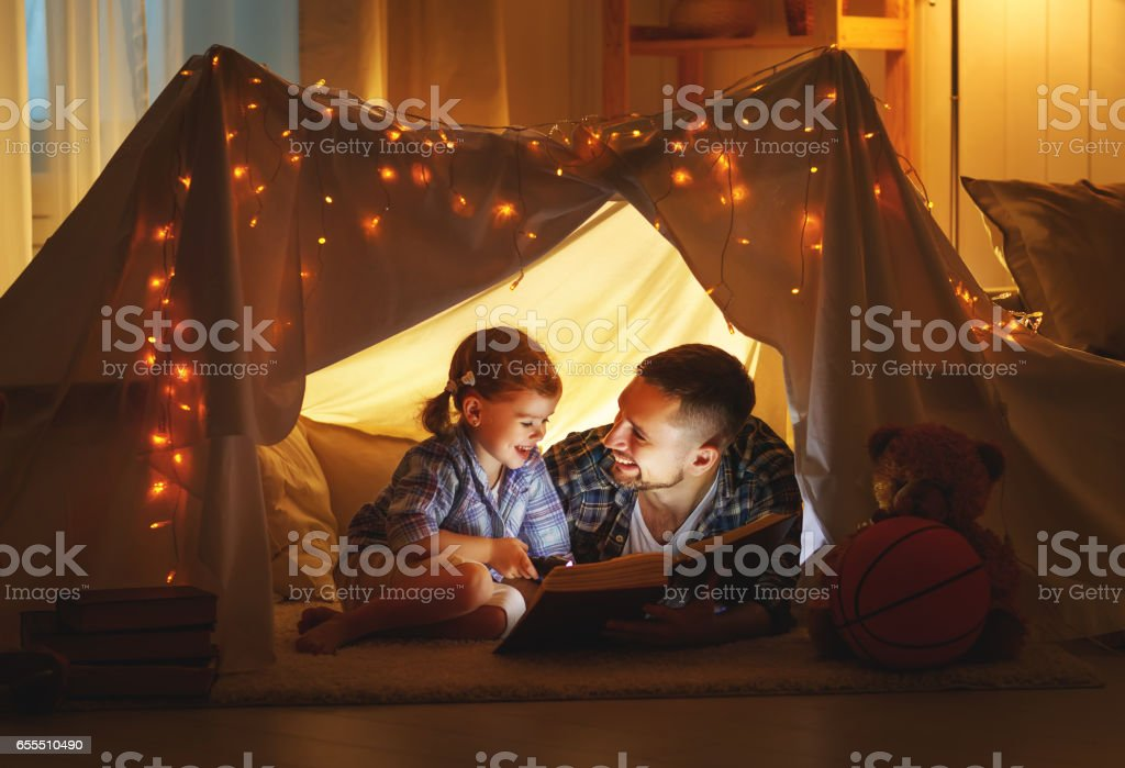 happy family father and child daughter reading a book  in  tent at home
